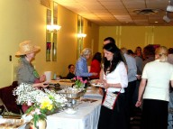 Jurate Krokys Stirbys and Regina Raubertas Serving Kugelis to Guests